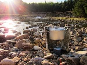 Kocher mit Windschutz am Fluss